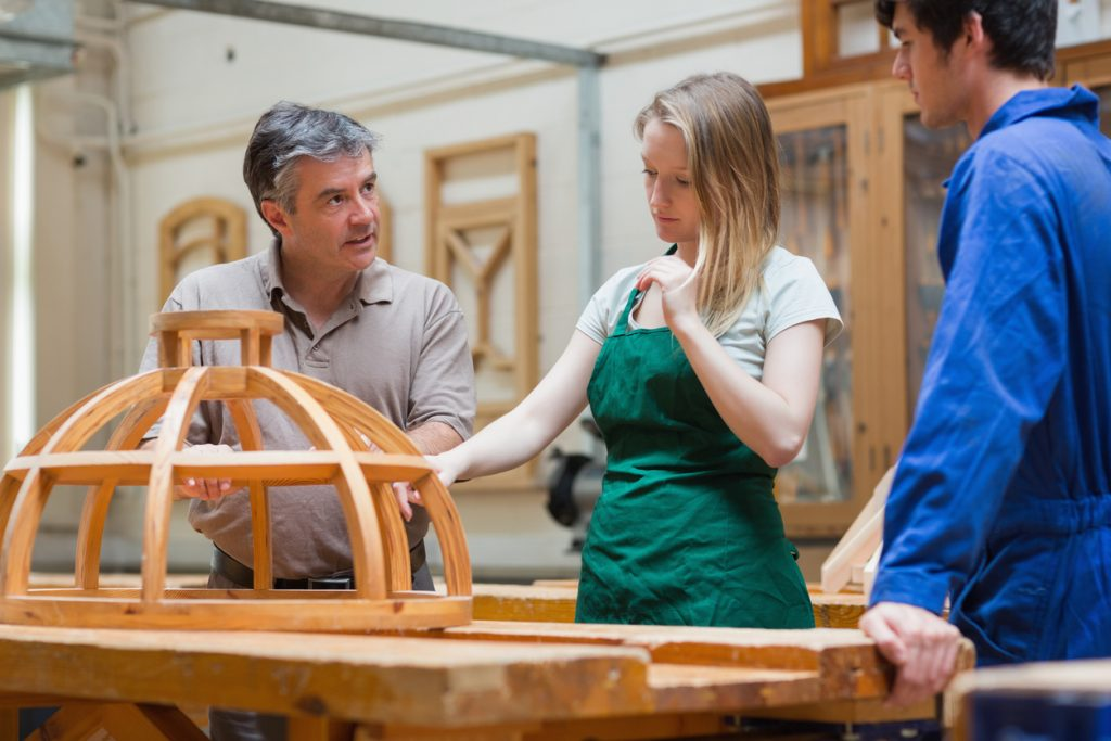 Carpentry Teacher showing students how to work wood in a woodworking class.